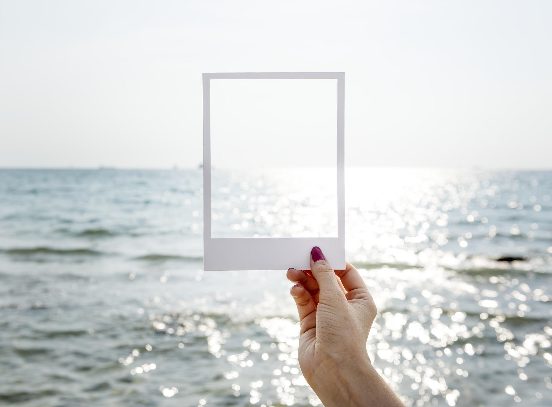 Eine weibliche Hand hält einen weißen Bilderrahmen hoch. Dahinter sieht man einen weiten Meeresblick. Ein Teil des Horizonts wird nun eingerahmt.