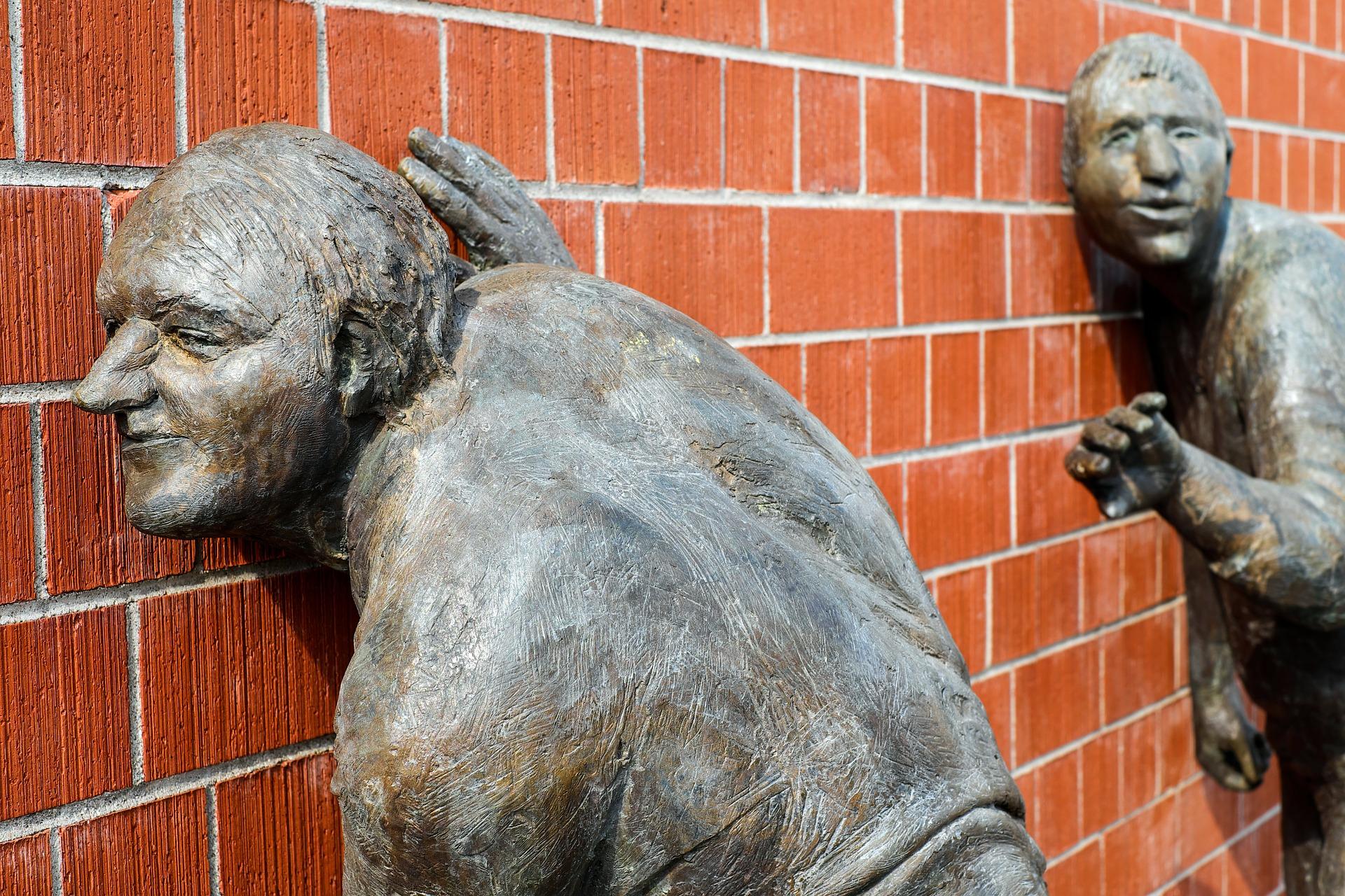 zwei Bronze-Statuen, sie lauschen an einer Wand