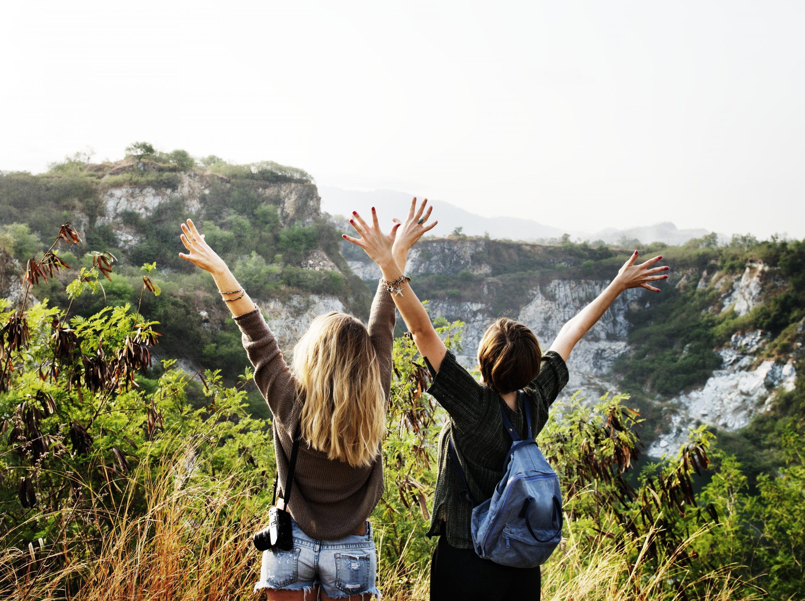 Zwei Frauen stehen auf einem Berg, sie heben die Arme in die Luft und freuen sich
