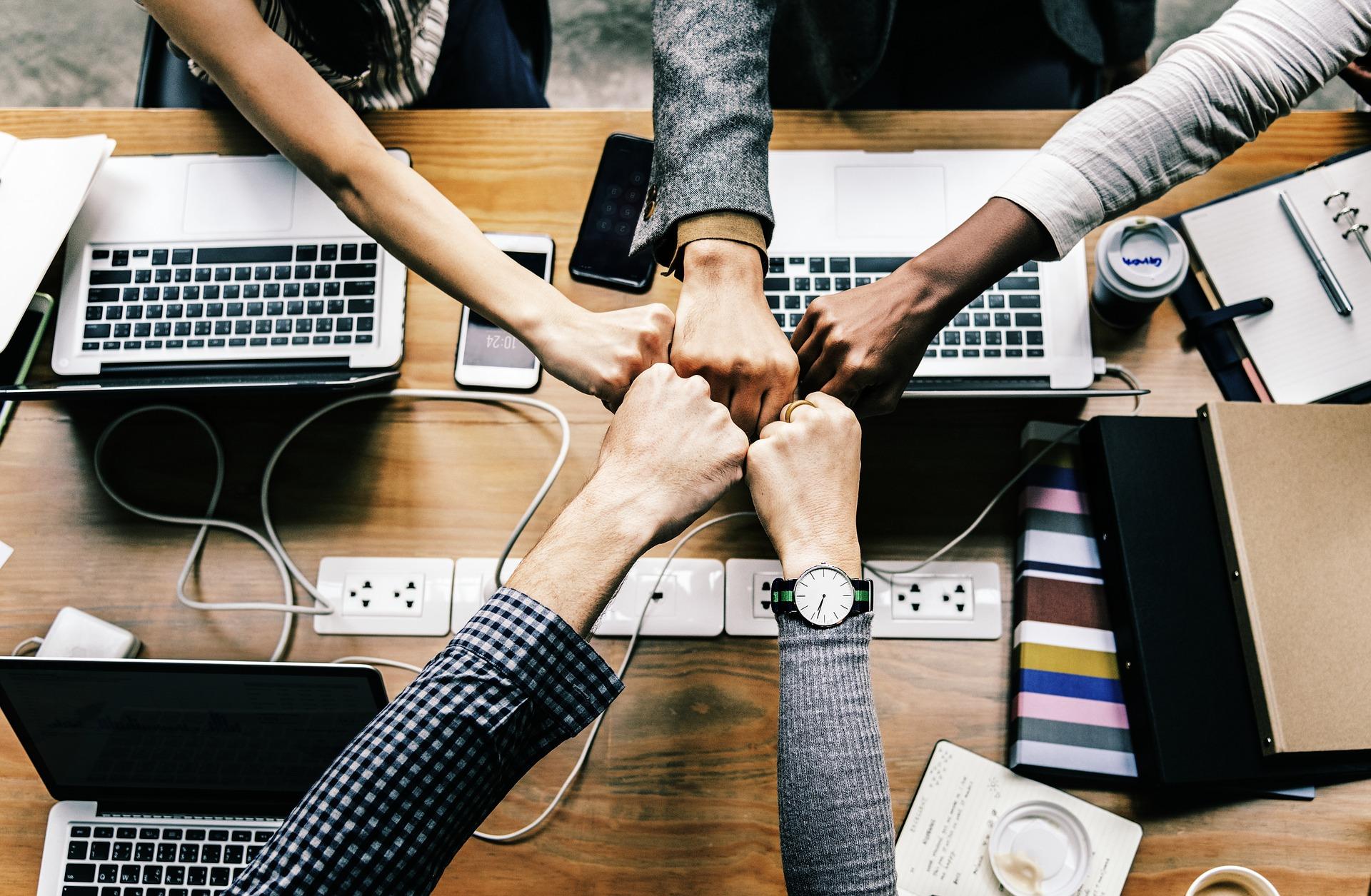 Über einem Tisch voll mit Laptops und Schreibkram sieht man fünf Hände, die sich einen Fistbump geben.
