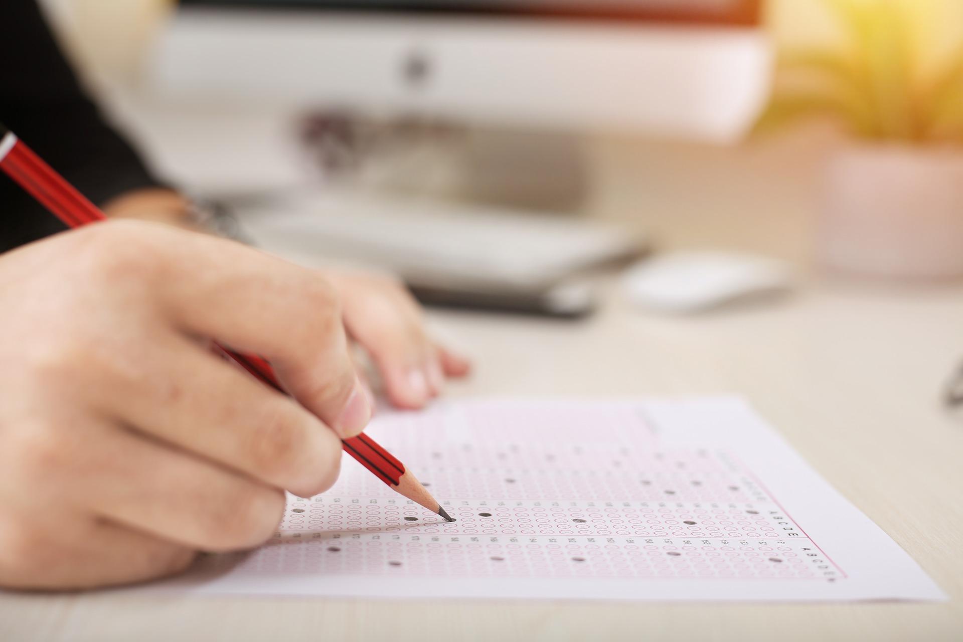 Eine Hand hält einen Stift und füllt Multiple-Choice-Fragen aus, warmes Licht im Hintergrund
