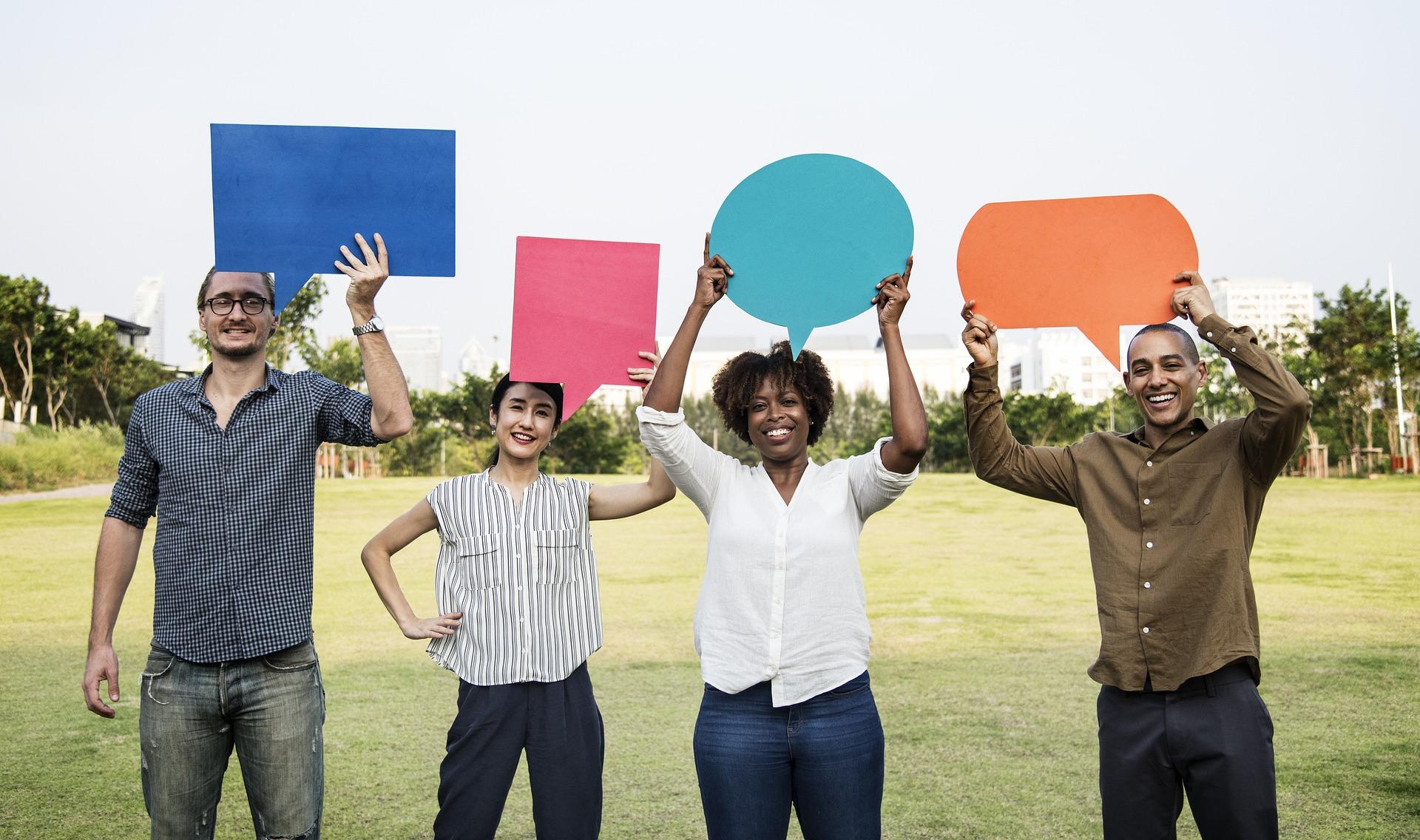 Vier Menschen halten Sprechblasen aus Papier hoch, sie stehen in einem sonnigen Feld. das Bild soll Feedback symbolisieren.