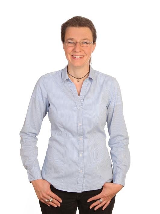 Ulrike Hanke steht da und lächelt. Sie hat dunkle Haare und trägt eine blaue Bluse.