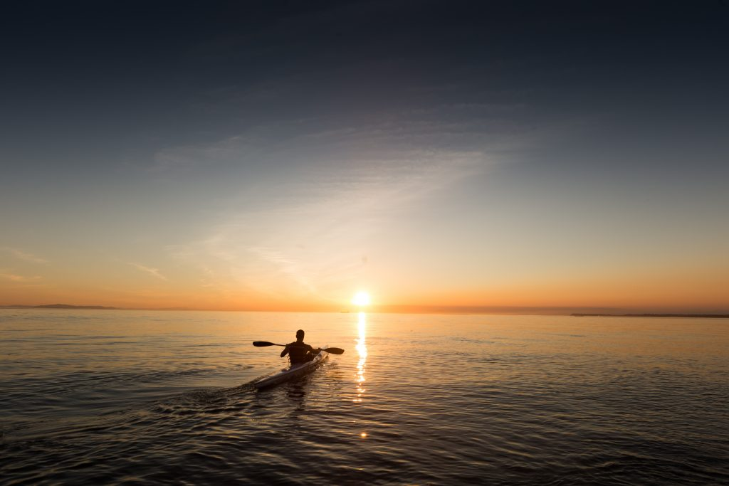 Die Achtsamkeit kann auch friedlich sein: Ein Mensch fährt Kanu auf einem großen See vor einem Sonnenuntergang